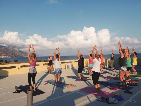 Grupa kobiet ćwiczy jogę na dachu budynku przy wschodzącym słońcu
